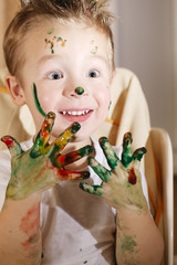 Cute excited boy with hands full of finger paint