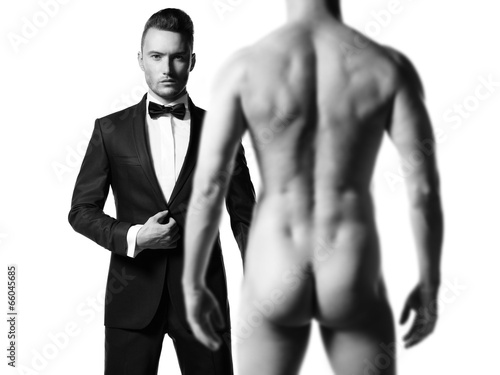 Man in suit in front of nude man