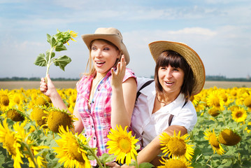 Beautiful women at summer at sunflowers field