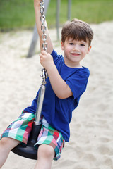 Little preschooler boy sitting on wire rope swing