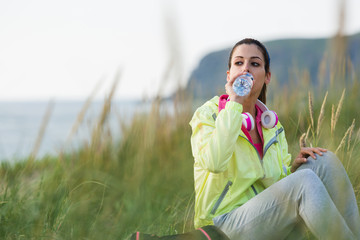 Relaxed fitness woman drinking water on workout rest