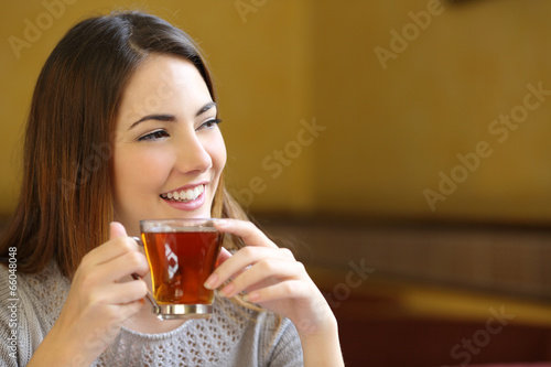 Happy woman thinking holding a cup of tea in a coffee shop - 66048048
