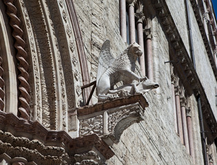 Perugia. Italy. Griffin sculpture on the facade of the building.