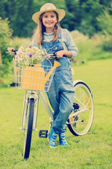 Cycling - girl with bicycle in the garden