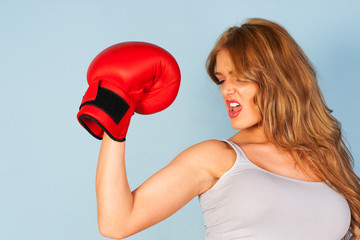 beautiful woman flexing arm muscles wearing a boxing glove