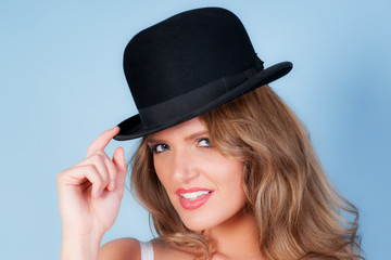 beautiful woman wearing a bowler hat on blue background