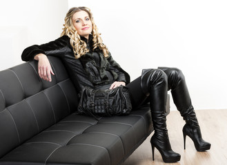 woman wearing fashionable black clothes sitting with a handbag o