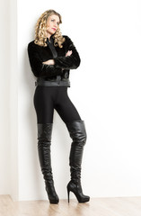 standing woman wearing fashionable black clothes and boots
