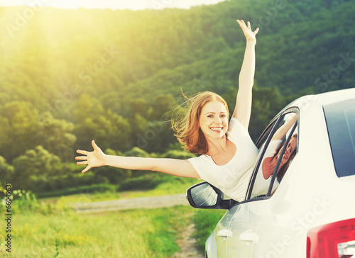 happy woman looks out the car window on nature - 66049631