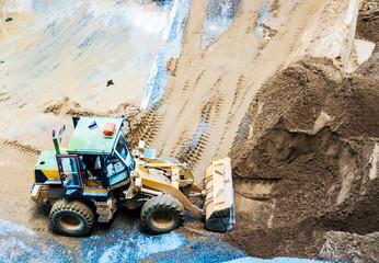 Wheel loader Excavator unloading sand and stone works at constru
