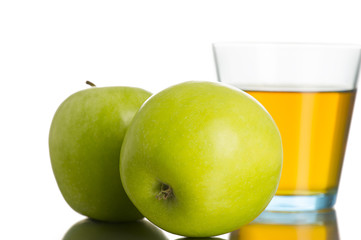 Two green apples next to a glass of apple juice