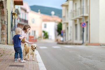 Two cute little sisters and a dog