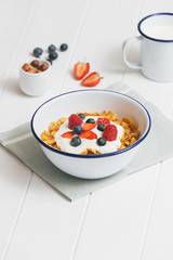 Healthy breakfast with cereals and berries in an enamel bowl