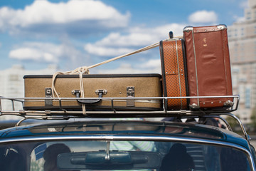 antique suitcases tied to the roof rack old car on blue sky