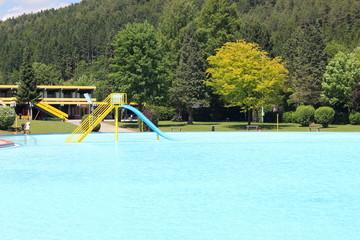 Riesiges Becken in einem Freibad mit einer Wasserrutsche