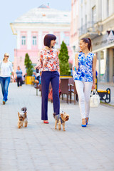 happy women walking the dogs on city street
