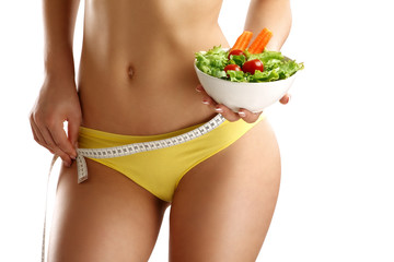 Close up of a woman measuring  hips with a salad in her hand