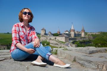 Woman siting in front castle in Kamenets-Podolsky, Ukraine