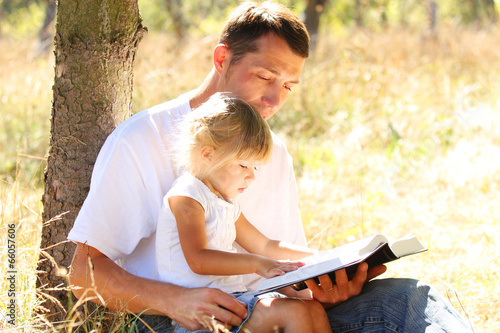 young father with his little daughter reads the Bible - 66057606