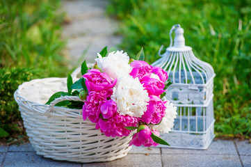 Still life with bunch of beautiful peonies in the basket