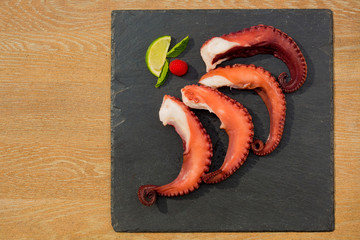 Cooked Octopus Plate with lime in black stone background