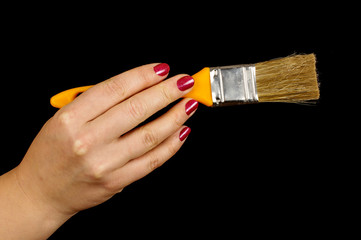 Female hand holding paintbrush isolated on the black background