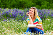 Young attractive girl studying in a flowery meadow.