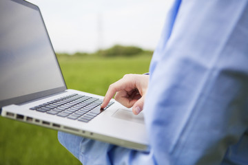 Laptop and hand on keyboard with nature background