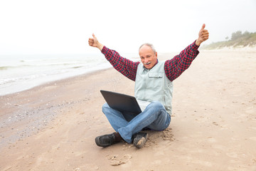 Happy old man on the beach with a laptop