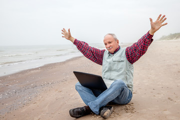 Old man with notebook on beach