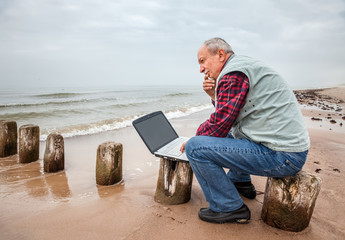 Thoughtful elderly man with the laptop