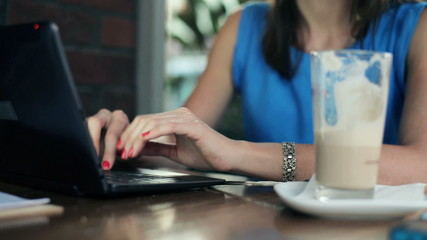 Female hands typing on laptop in cafe