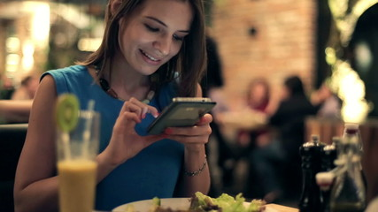 Woman taking photo of tasty salad with cellphone in restaurant