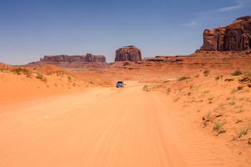 Dirt Road Through Monument Valley with a Vehicle in Distance
