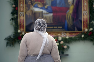 Woman  looking at the icon of the Dormition of the Virgin.