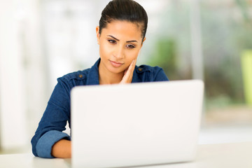 thoughtful young woman looking at the laptop screen