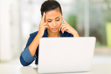 unhappy young woman looking at computer screen