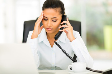 confused office worker talking on telephone