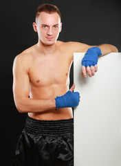 Young handsome boxer man standing near board , isolated on black