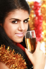 Beautiful young brunette woman drinking champagne at christmas