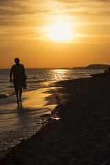 Uomo che cammina su spiaggia al tramonto