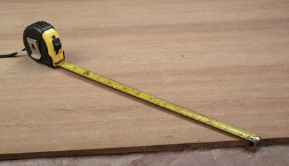 A tape measure extended on a wooden tabletop.