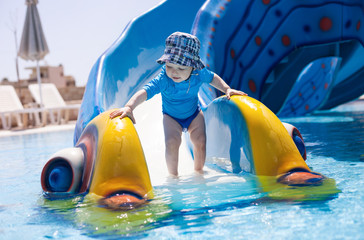 Toddler boy standing at the bottom of water slide