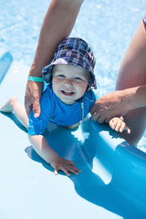Baby boy having fun on a water slide
