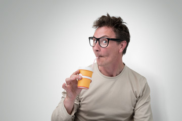 Funny man in glasses drink through a straw