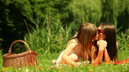 Little daughter kissing her mother on the meadow
