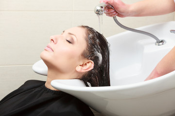 Hairstylist washing woman hair. Hairdressing beauty salon