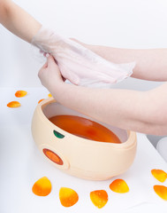 Hand orange paraffin wax in bowl. Manicure beauty spa salon