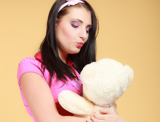 Childish woman infantile girl in pink kissing teddy bear toy