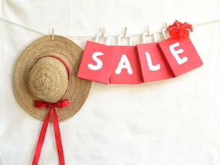 Red bargain sale shopping bags with straw hat
